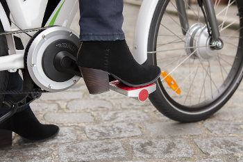 girl wearing boots shown on bike with smart pedal
