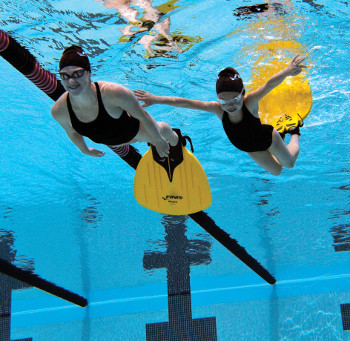 Woman and child finswimming with monofins in a swimming pool